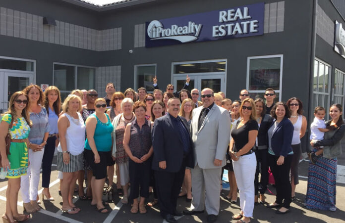 Brokers/owners Rui Alves and Fedele Colucci, along with their salespeople and staff, celebrate the opening of a new Georgetown, Ont. office.