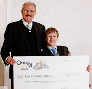 Century 21 founder U. Gary Charlwood presents the cheque to Easter Seals National Ambassador Brandon Liston.