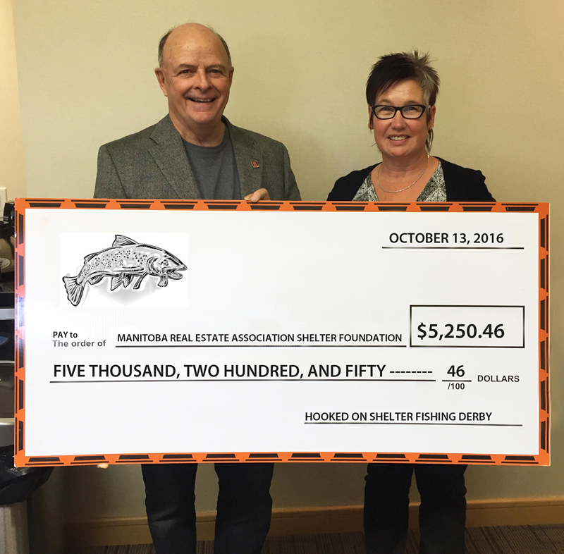 Donna Kirsch of Gateway Real Estate and MREA Shelter Foundation chair Brian Canart with the cheque from the fishing derby.
