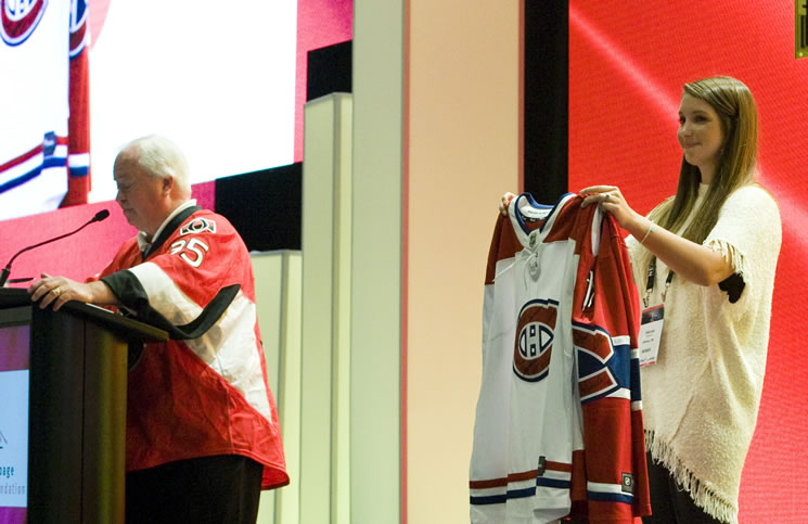 Kent Browne has help from his daughter Hanna Browne, broker with Royal LePage Team Realty, in auctioning off a Montreal Canadiens package at the Royal LePage National Sales Conference's Shelter Live Auction Lunch.