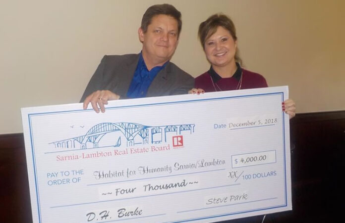 Steve Park, president of Sarnia-Lambton Real Estate Board, and Kathy Murphy, PR & communications chair, with the cheque for Habitat For Humanity.