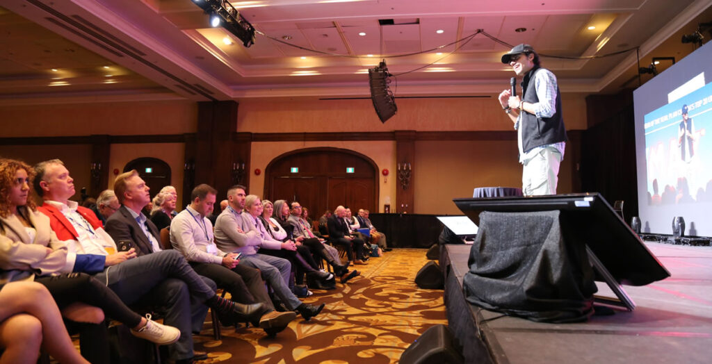 """Manu """"Swish"""" Goswami addresses the Re/Max Active Conference."""