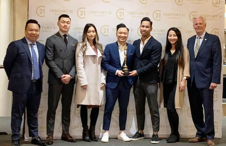 Stephen Chow, broker of record, Century 21 Atria Realty in Toronto, left, and Brian Rushton, EVP of Century 21 Canada, right, present the Grand Centurion Team award to The Wolf Pack team from Century 21 Atria Realty.