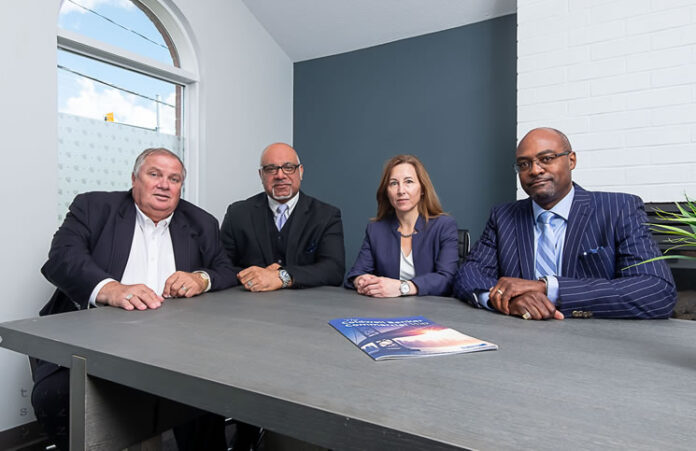 "Pictured is the Coldwell Banker RMR Commercial team (""Our suits,"" says sales rep Shawn Lackie) at the boardroom table used in the Suits TV series. From left: Graham Healer, Armani Bhatti, Tracy Hammer and Michael Goulbourne."