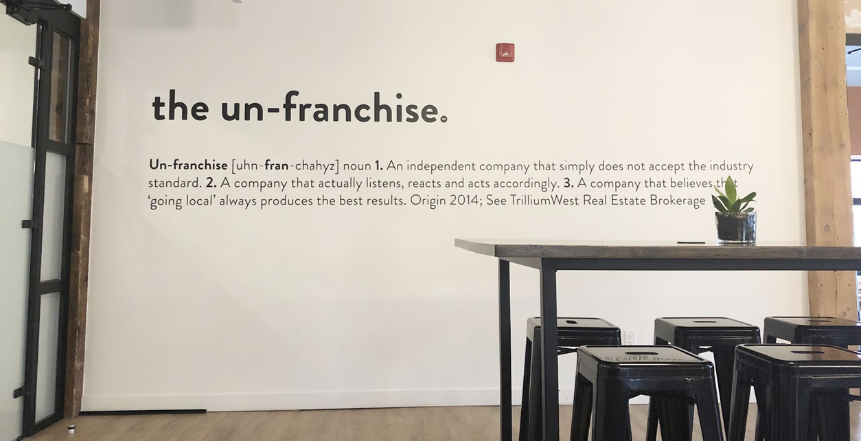 """TrillumWest's """"un-franchise"""" motto is painted on their wall."""