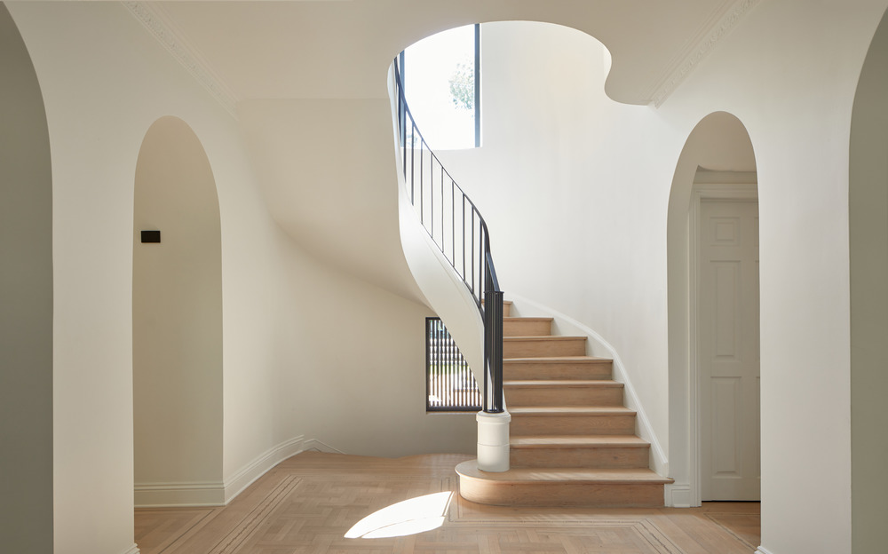 The railing of the central staircase has been treated in a minimalist way to direct attention to the curves around the staircase, as well as the rounded openings in the ceiling.